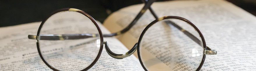 Old glasses on antique book